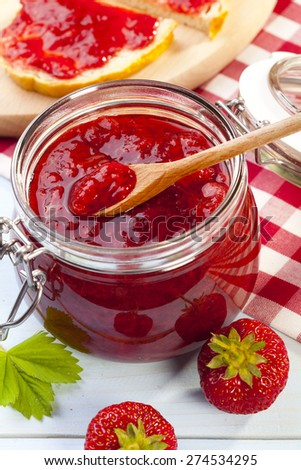 Home made strawberry jam on blue woodboard - stock photo