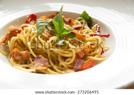 Home made style spaghetti chili garlic and bacon on white ceramic plate