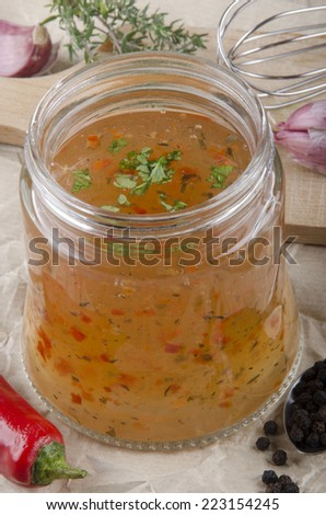 home made vinaigrette in a glass with chopped parsley - stock photo