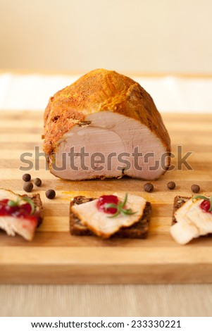Home-made whole boiled chicken ham prepared by polish butcher. Presented on a wooden desk-board. Part of ham is cut to slices, showned with cranberries marmalade. - stock photo