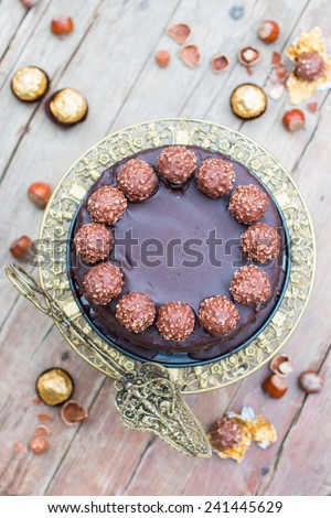 Home made whole chocolate cake with chocolate icing and famous italian chocolates - stock photo