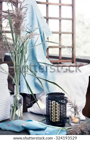Home marine style accessories: candle lantern, cushions, textiles for comfortable rest in the garden, terrace, balcony. Natural light photo. Toned photo. - stock photo