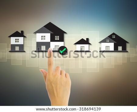 Home model and hand on dark background.