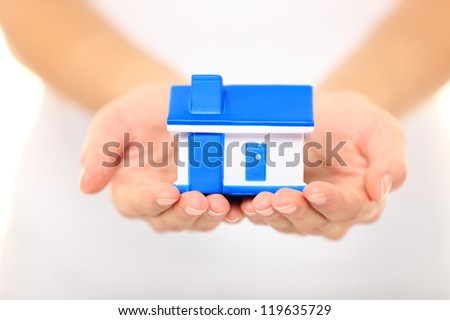 Home - new house concept. Woman holding model house - stock photo