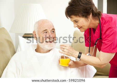 Home nurse giving her elderly patient a glass of orange juice. - stock photo