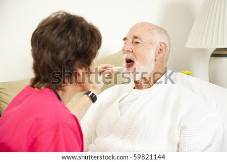 Home nurse uses a thermometer to take an elderly patient's temperature.