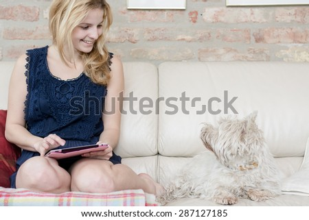 Home office, blonde girl using tablet - stock photo