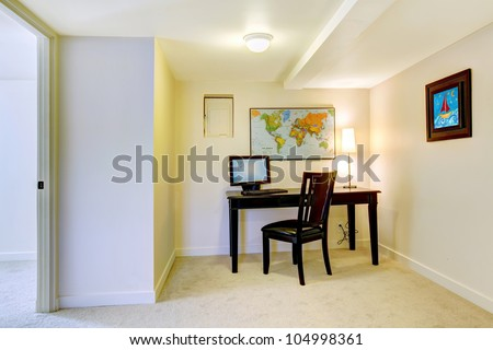 Home office desk with map on the white wall and art. - stock photo