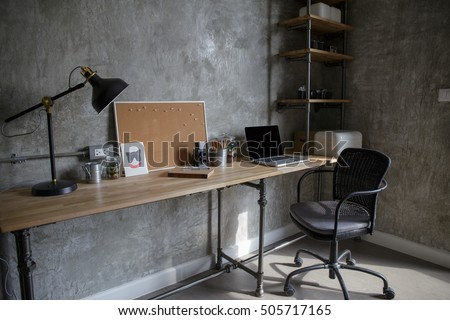 Home office interior in loft space with wooden table, office supplies, documents, notebook and laptop,
