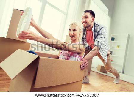 home, people, moving, time and real estate concept - happy couple having fun and riding in cardboard boxes with clock at new home - stock photo