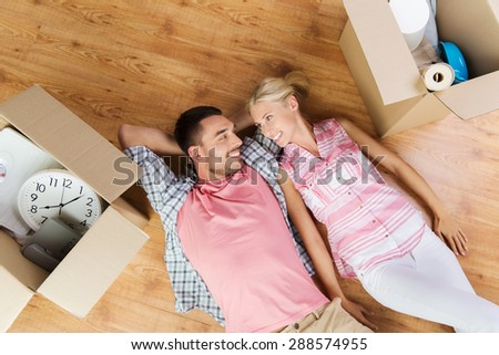 home, people, repair and real estate concept - happy couple with cardboard boxes and stuff lying on floor to new place