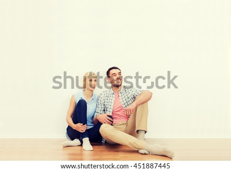 home, people, repair, moving and real estate concept - happy couple of man and woman sitting on floor and dreaming at new place - stock photo