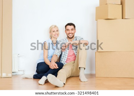 home, people, repair, moving and real estate concept - happy couple with many cardboard boxes sitting on floor at new place - stock photo