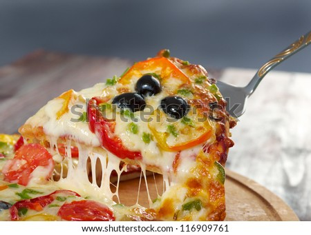 home pizza with tomato and eggplant  Closeup .taking slice of pizza,melted cheese dripping - stock photo