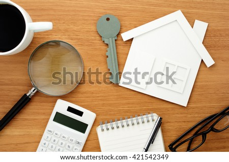 Home planning. Calculating and checking. House and key shaped paper cutout, calculator and magnifier on wooden table.  - stock photo