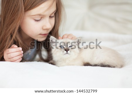 Home portrait of adorable child with small kitten resting on a soft sofa - stock photo