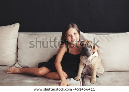 Home portrait of cute child hugging with puppy of Chinese Shar Pei dog on the sofa against black wall - stock photo