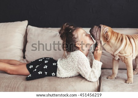 Home portrait of cute child kissing puppy of Chinese Shar Pei dog on the sofa against black wall - stock photo