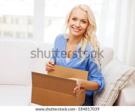home, post, delivery and happiness concept - smiling young woman opening cardboard box at home - stock photo
