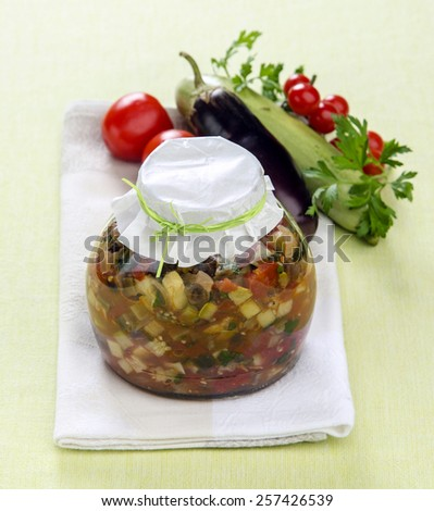 home preservation ratatouille with herbs in a glass jar with vegetables in the background - stock photo