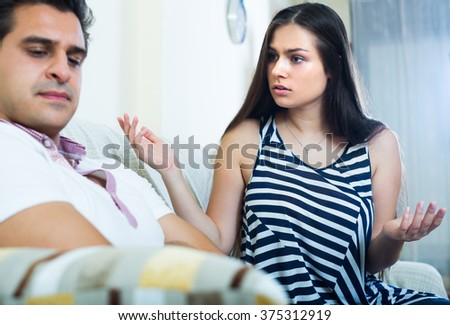 Home quarrel between offended husband and his young longhaired wife - stock photo