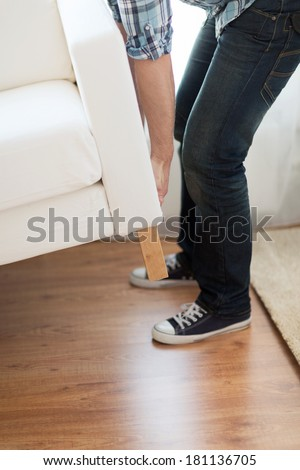 home, real estate and furniture concept - close up of male lifting up sofa to move - stock photo