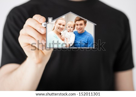 home, real estate, family and technology concept - man and sign of family with child and dream house - stock photo