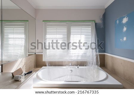 Home renovation of residential bathroom with large tub showing paint roller and sanding block - stock photo