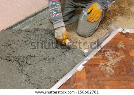 Home renovation, worker finishing concrete with trowel - stock photo