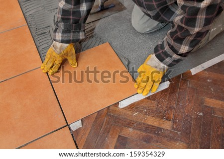 Home renovation, worker placing tile to floor - stock photo