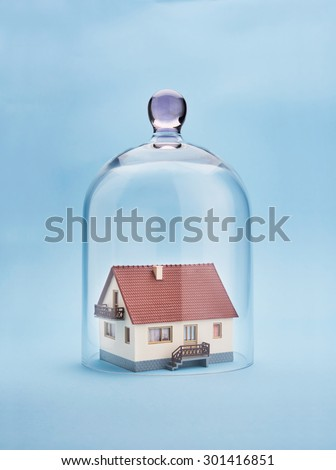 Home safety. A model home protected under a glass dome on blue background - stock photo