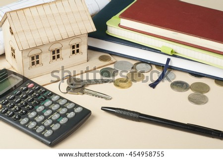 Home savings, budget concept. Model house, notepad, pen, calculator and coins on wooden office desk table - stock photo