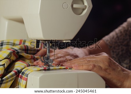 Home Sewing. Elderly woman working at the electromechanical sewing machine. - stock photo
