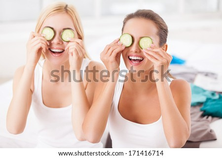 Home spa. Two beautiful young women holding pieces of cucumber on their eyes and smiling while sitting on the bed