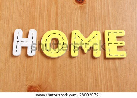 HOME, spell by woody puzzle letters with woody background - stock photo