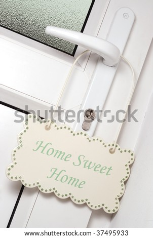 Home sweet home sign hanging on a door handle - stock photo