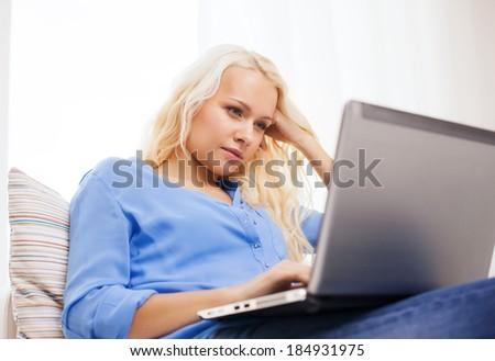 home, technology and internet concept - woman sitting on the couch with laptop computer at home