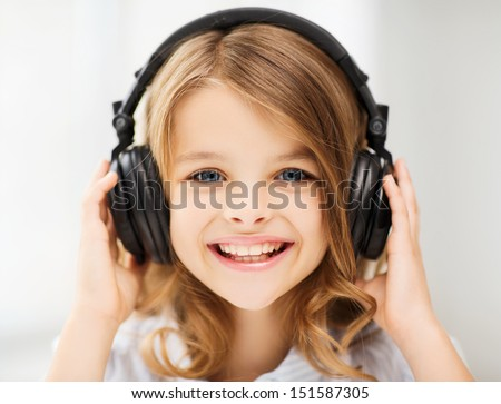 home, technology and music concept - little girl with headphones at home - stock photo