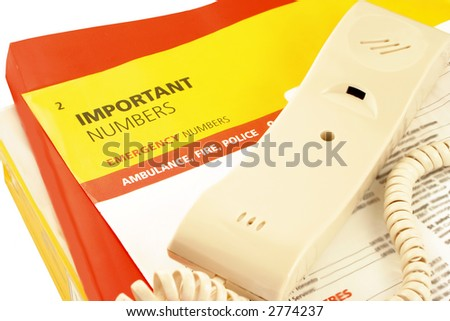 home telephone on top of phone directories and emergency numbers - stock photo