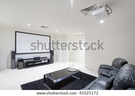 home theater room with black leather recliner chairs, black rug and table with wine glasses - stock photo