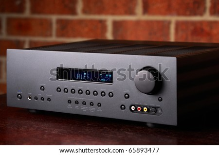Home Theatre Amplifier A high end Hi-Fi Home Theatre Amplifier with a red brick wall backdrop. Black enclosure with blue LCD display. - stock photo