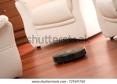 Home vacuum cleaning robot in action on genuine living room wooden floor. Selective focus on robot. - stock photo