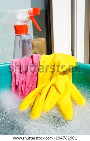 home window washer set - yellow rubber glove, wet rag, spray glass cleaner bottle, foamy water in green basin on windowsill - stock photo