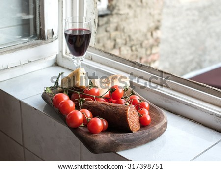 Home wine appetizer set. Glass of red wine, Hungarian spicy sausage, farmers cheese and cherry-tomatoes in a rustic wooden dish set in front of window, selective focus - stock photo