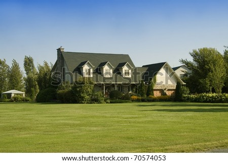 Home with beautiful landscaping in the country - stock photo