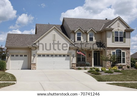 Home with covered entry and double three car garage - stock photo