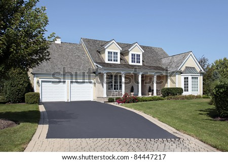 Home with front porch and partial brick driveway - stock photo