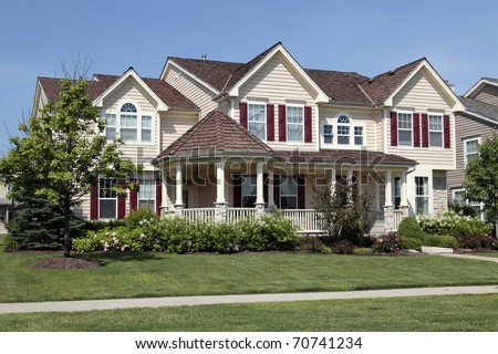 Home with front porch and red shutters - stock photo