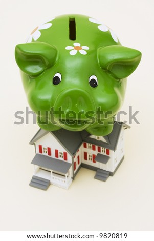 Home with piggy bank sitting on it – home finance weighing you down