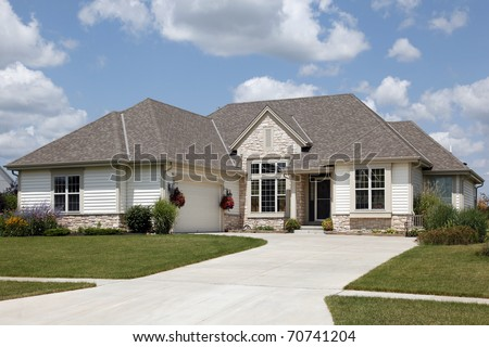 Home with stone entry and cream colored siding - stock photo